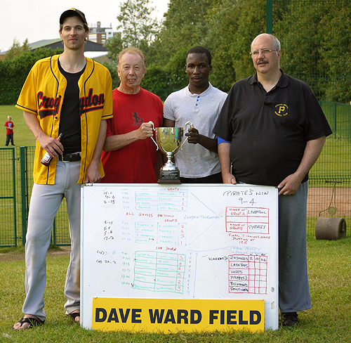 Left to right: Conor Riffle (tournament coach), Dave Ward, young pitcher/shortstop Tim Ssali, and club helper Mark Goater.